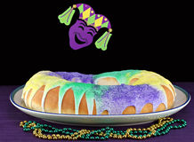 Kings Cake in Mardi Gras Setting. King's Cake in honor of the three kings. Original colors of green for faith, gold for power and purple for justice
