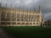 Kings college Cambridge under a stormy sky. Kings college Chapel under storm clouds, featuring a person in the foreground walking across the grass Stock Photo