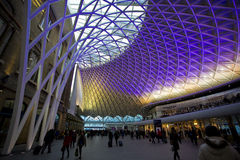 Kings Cross Station. The purple illuminated ceiling of King's Cross Railway station, passengers visible Stock Photography