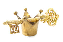 Kings crown. Golden crown with golden key isolated over white Royalty Free Stock Photo