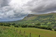 Kings Mountain in Sligo Ireland. Green fields and dramatic clouds with Kings Mountain on background in Sligo Ireland Stock Photo