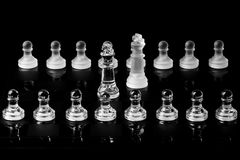 Kings in negotiation. Frosted glass and clear glass chess pieces with kings in negotiation and pawns in the background Royalty Free Stock Images