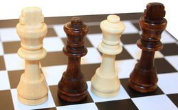Kings and Queens. 4 chess figures - 2 queens and 2 kings. Standing close to each other, divided by two stock photography