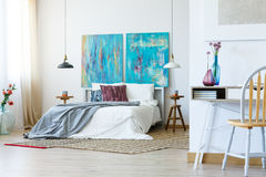 Kingsize bed, bloemen en schilderijen Royalty-vrije Stock Foto's