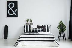 Kingsize bed tussen skateboard en installatie stock fotografie
