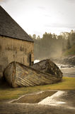 Kingston, Norfolk Island. An old lighter (small boat used to ferry cargo) against a stone building from the convict settlement in the world heritage listed area royalty free stock photography