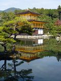 Kinkaku-ji, The Golden Pavilion, reflects in a pond in Kyoto, Japan. Trees and hilltops reflect in the pond Stock Photography