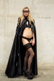 Kinky beauty in lingerie with gothic cape and mask Royalty Free Stock Photography