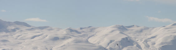 Snowy mountain range panorama. Panorama of Kinnarfjoll mountain range late winter, with snow. Snowy mountains on the skyline horizon. Blue and white mountainous stock photo