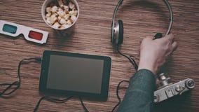 Kino und Unterhaltungs-Konzept, Mann nimmt Kopfhörer, Draufsicht stock footage