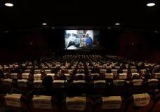 Kino voll von den Leuten, die einen Film aufpassen Stockfotos