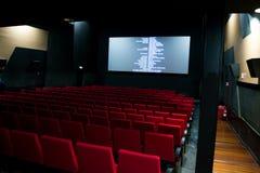 Kinoleinwand und rote Stühle innerhalb eines Kinos Lizenzfreie Stockbilder