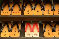 Kinosaki Japan - Juni 17, 2011: Rader av traditionella japangeta-sandaler på ingången till en offentlig varm vår Arkivbild