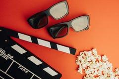 Kinowy minimalny pojęcie Oglądać film w kinie clapper deska, 3d szkła, popkorn Fotografia Royalty Free