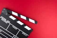 Kinowy minimalny pojęcie Oglądać film w kinie clapper deska na czerwonym tle Zdjęcia Royalty Free