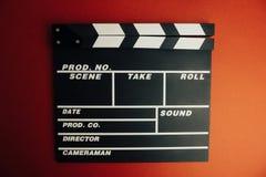 Kinowy minimalny pojęcie Oglądać film w kinie clapper deska na czerwonym tle Zdjęcie Stock