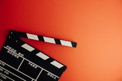 Kinowy minimalny pojęcie Oglądać film w kinie clapper deska na czerwonym tle Obraz Royalty Free