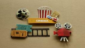 Kinozeichen mit Gläsern der Popcornwanne 3d, die Film Projektor auf etikettiert, bräunen Hintergrund lizenzfreie stockfotografie