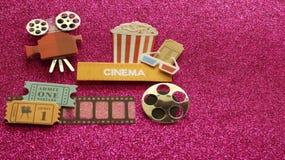 Kinozeichen mit Glas-Filmkarten des Popcorneimers 3d auf Filmstreifen mit einer Spule auf einem dunklen rosa Hintergrund lizenzfreies stockfoto