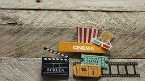 Kinozeichen mit Glasfilm-Kartengroßleinwand des Popcorneimers 3d öffnete Kasten auf hölzernem Hintergrund lizenzfreie stockfotografie