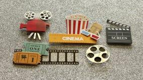 Kinozeichen mit Popcorneimer-Filmkarten auf Filmstreifen auf silbernem gefunkeltem Hintergrund lizenzfreies stockbild