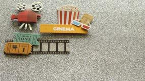 Kinozeichen mit Popcorneimer-Filmkarten auf Filmstreifen auf silbernem gefunkeltem Hintergrund lizenzfreie stockfotografie