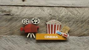 Kinozeichen mit Popcorneimer-Filmprojektor auf hölzernem Hintergrund stockbild