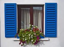 Kinsale window blue shutters. Flowers and blue shutters on window in the fishing village of kinsale Stock Images