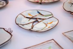 Kintsugi style handcrafted plate sold at handicraft market. Kintsugi is the Japanese art of repairing broken pottery stock photos