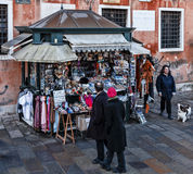 Kiosk with Souvenirs in Venice. Venice,Italy- February 12, 2012: People passing by a kiosk full of various souvenirs on a small street in Venice Stock Photography