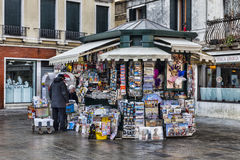 Kiosk in Venice. Venice,Italy- February 18, 2012: Two old men arranging a kiosk full of magazines and souvenirs in a town square in Venice Royalty Free Stock Image