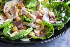 Kip Caesar Salad in Zwarte Kom Stock Foto's