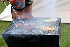 Kip en hamburgers die op een traditionele lumpwoodcharco koken stock foto's