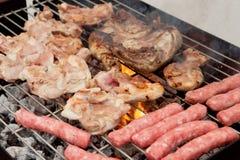Kip en worsten op de barbecue Stock Fotografie