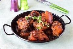 Kip met gedroogde pruimen in de oven in een zwarte kom op een textielachtergrond worden gekookt die stock afbeeldingen