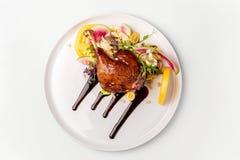 Kip met groenten op witte gediend die plaat met bessensaus wordt bedekt royalty-vrije stock afbeeldingen