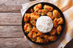 Kip in oranje saus met rijst op een plaat De horizontale bovenkant wedijvert Stock Foto's