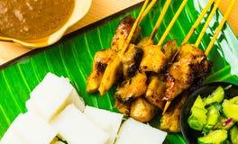 Kip satay met kubieke rijst, de saus van de atjar en kerrieboon Stock Foto's