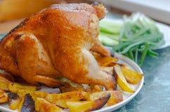Kip van de oven op een witte plaat met greens en aardappels met een gouden korst royalty-vrije stock afbeelding