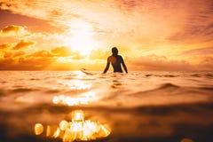Kipieli kobieta w oceanu czekania fala przy zmierzchem lub wschodem słońca Zima surfing w oceanie Obraz Stock