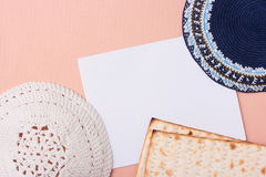Kippahs. A blue and a white kippah laying next to matzah and a piece of paper. Add your text to the paper Royalty Free Stock Photography