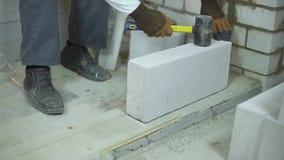 Kippen Sie oben vom Erbauer, der ersten Block entsprechend Kennzeichen auf Bodengrundlage legt stock video