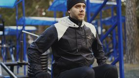 Kippen Sie oben vom jungen Athletenmann, der Übung Turnhalle an der im Freien im Winterpark tut stock video footage
