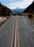 Kippen Sie Schicht-Objektiv-Straße mit Autos und Berg Stockbilder