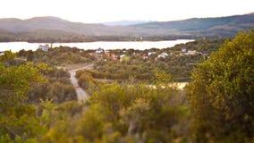 Kippen Sie Schiebelandschaft einer kleinen Stadt nahe bei einem See in den Bergen lizenzfreies stockfoto