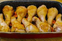 Kippenbenen die op de braadpan in de oven worden gebakken stock fotografie
