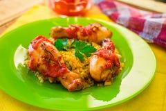Kippenbenen met tomaat-oranje saus, rozemarijn en rijst Stock Afbeelding