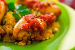 Kippenbenen met tomaat-oranje saus, rozemarijn en rijst Stock Foto