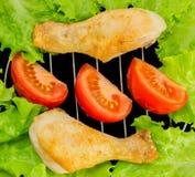 Kippenbenen op de grill met tomatenplakken en slaop mening Royalty-vrije Stock Afbeeldingen