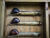 Kippendes Füllen des Bambusses mit heißem Wachs für das zeichnende Batikmuster angezeigt auf hölzernes Kasten Foto eingelassenem  lizenzfreie stockfotografie
